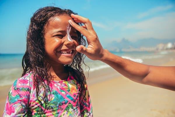 Applying sunscreen to a girl's face.